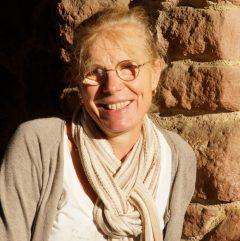 Véronique Stirn adossée à un mur de pierres